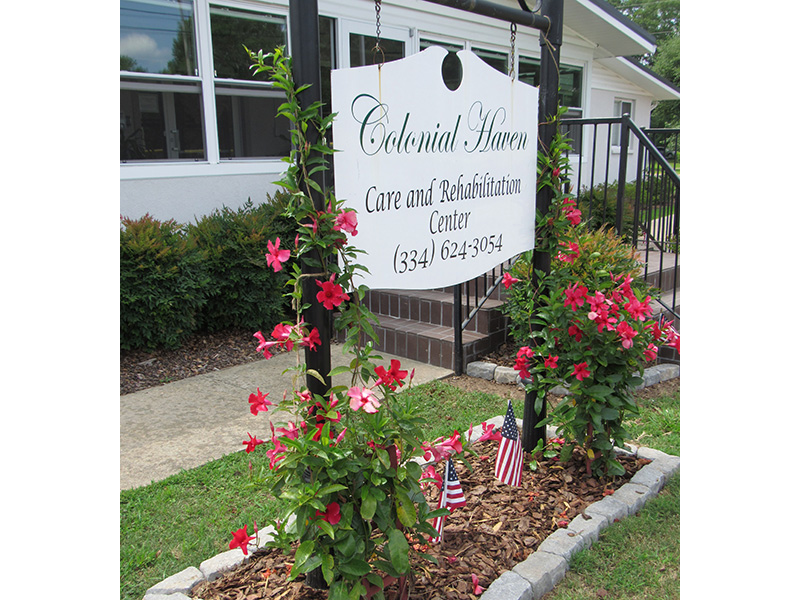 Colonial Haven front entrance sign with blooming flowers and vines