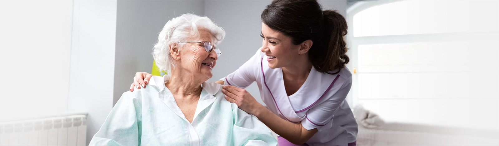 Smiling nurse wearing lavender scrubs with her hands on a resident's shoulders