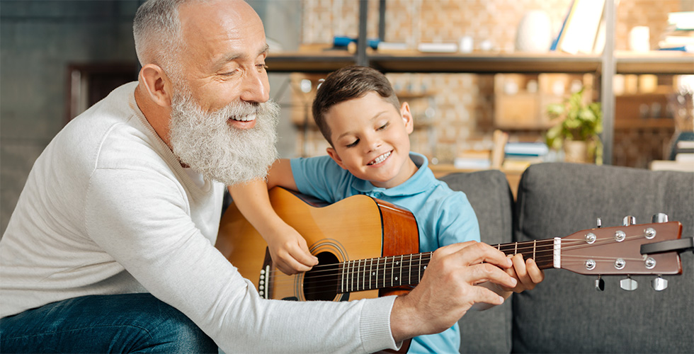 A senior assisting a young boy with learning how to play a guitar.