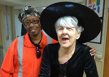 A nurse and a resident dressing up for halloween in a witch outfit and a orange vest