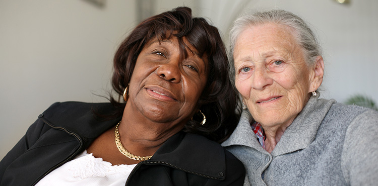 Two elderly women smiling and hugging