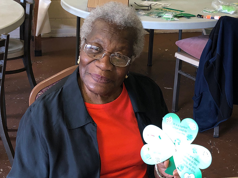 Sweet and smiling resident showing off the finished clover decoration
