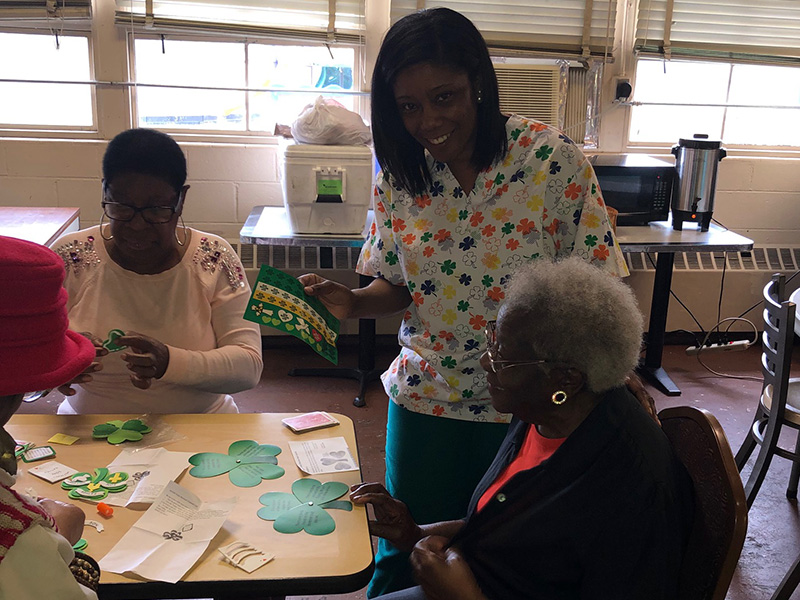 Nursing staff wearing four leaf clover scrubs and helping with St. Patrick's Day activities