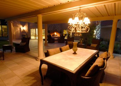 Elegant, covered seating outside with a fireplace in the background