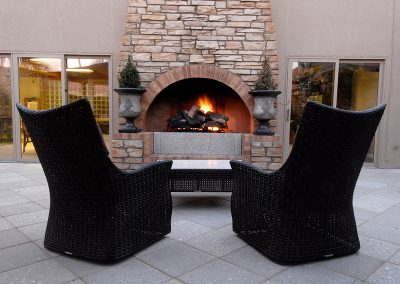 Resident seating in front of a large fireplace outdoors
