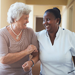 Nurse and resident walking down a hallway smiling and chatting wit each other