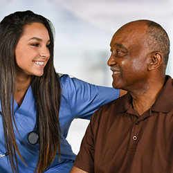 Smiling nurse checking in with a long-term resident to see how he's feeling
