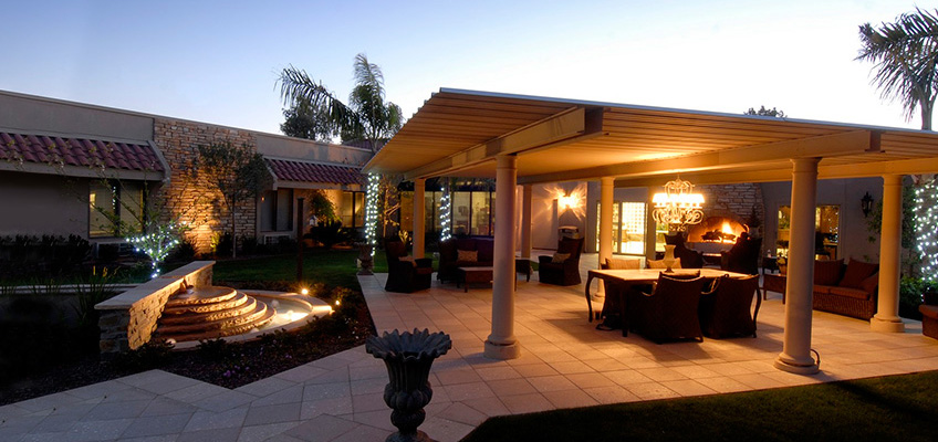 Well lit patio at night with covered seating and an outdoor water feature
