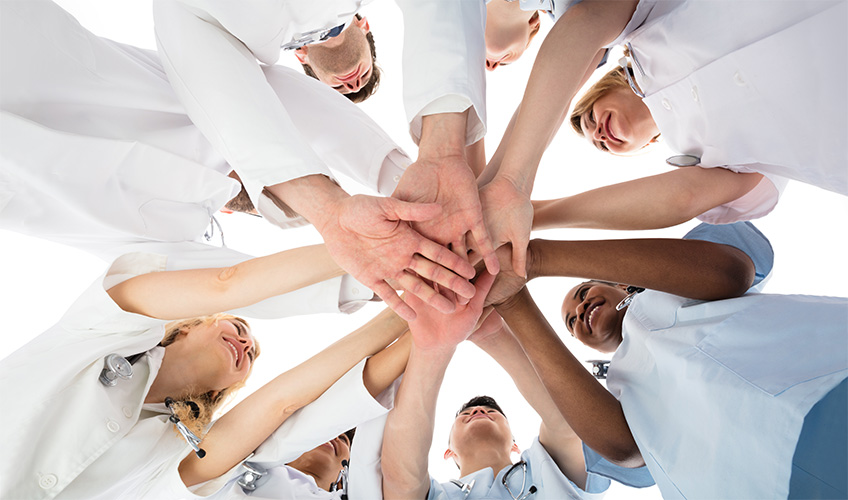 Staff putting their hands together in a circle