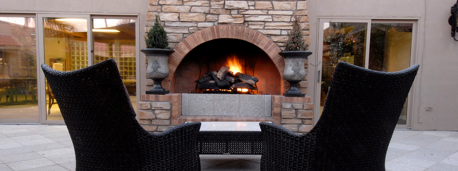 Two chairs positioned in front of an outdoor fireplace with stacked stone and trees flanking both sides