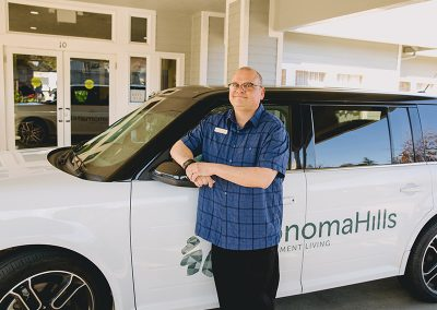 Sonoma staff member in front of the transportation car for residents