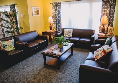 Beautiful lounge area for residents with comfortable leather couches and chairs