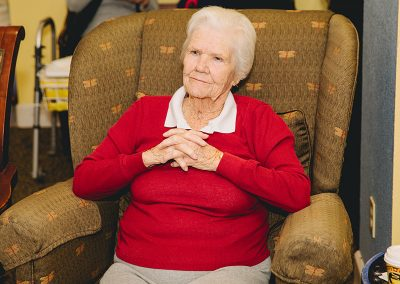 A resident sitting peacefully with her arms folded in a comfortable chair
