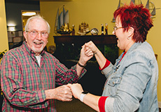 A resident and staff member dancing together and laughing