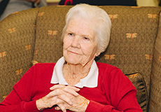 A resident sitting comfortably in a chair with her arms folded