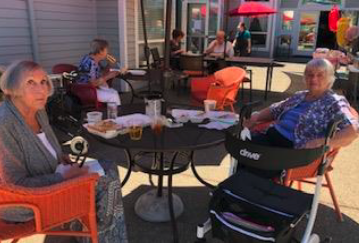 Residents Enjoying A BBQ Outside Together.