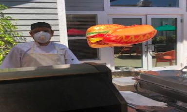 Staff Member With A Mask On Grilling Outside