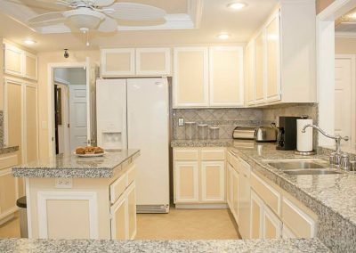 Beautiful kitchen with granite countertops and a center island with snacks available