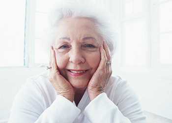 A woman with her hands resting on her cheeks with a smile on her face