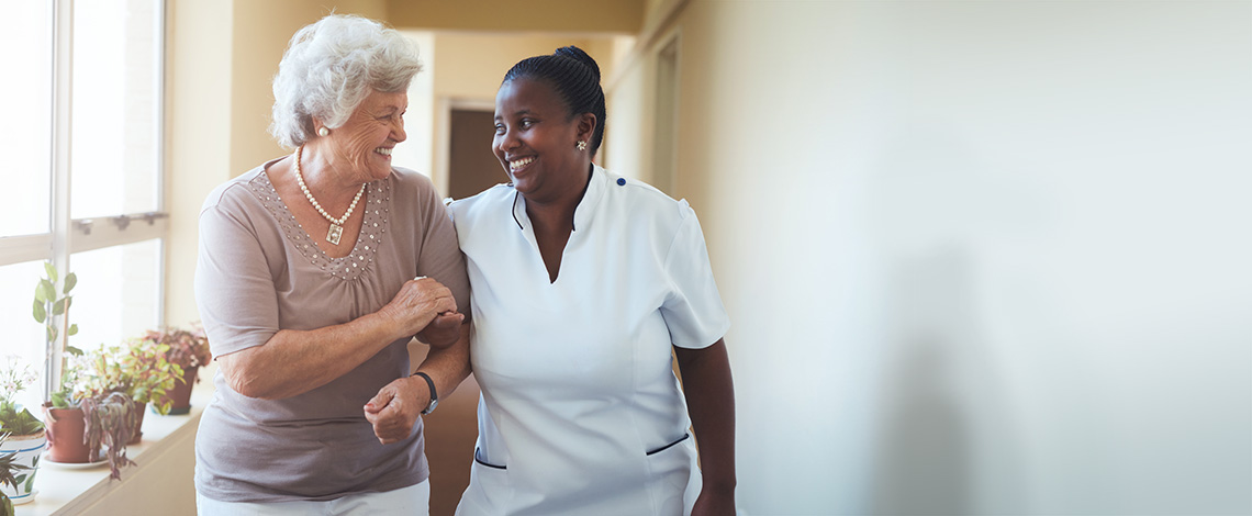 A nurse walking down a hall with an elderly patient
