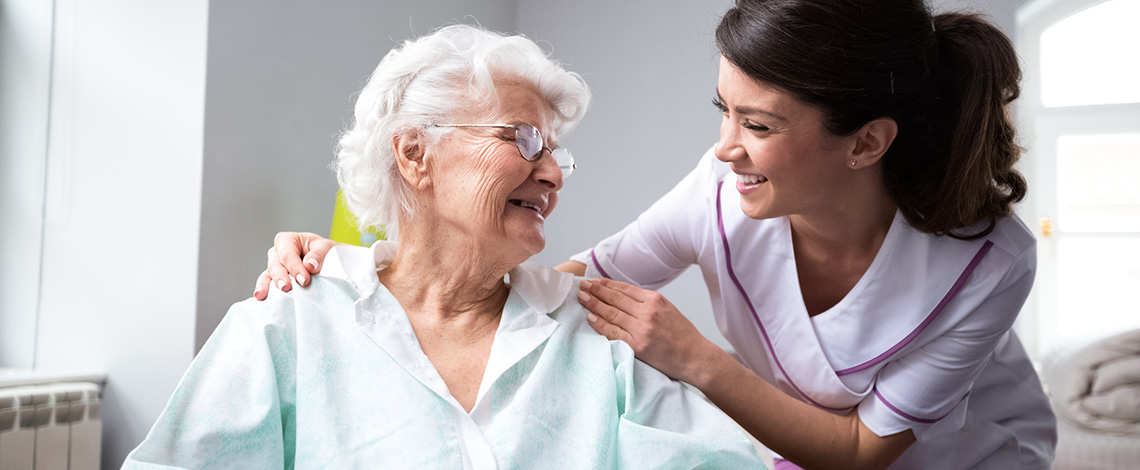 A nurse leaning in toward an elderly woman with a smile on her face.