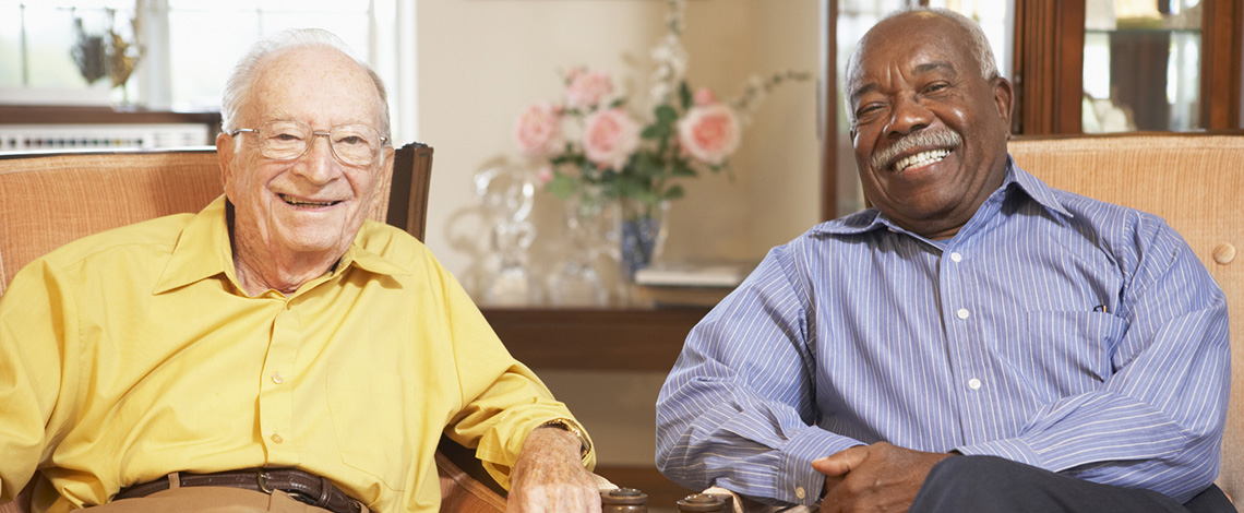 Two men sitting together on a couch smiling