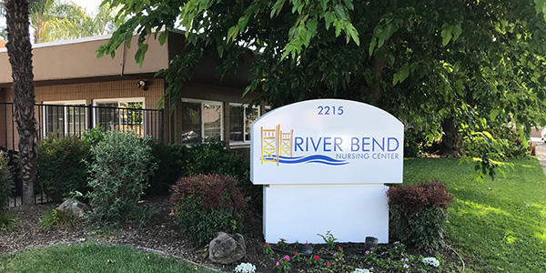 The River Bend Nursing Center sign in front of the building surrounded by lush grass and plants.
