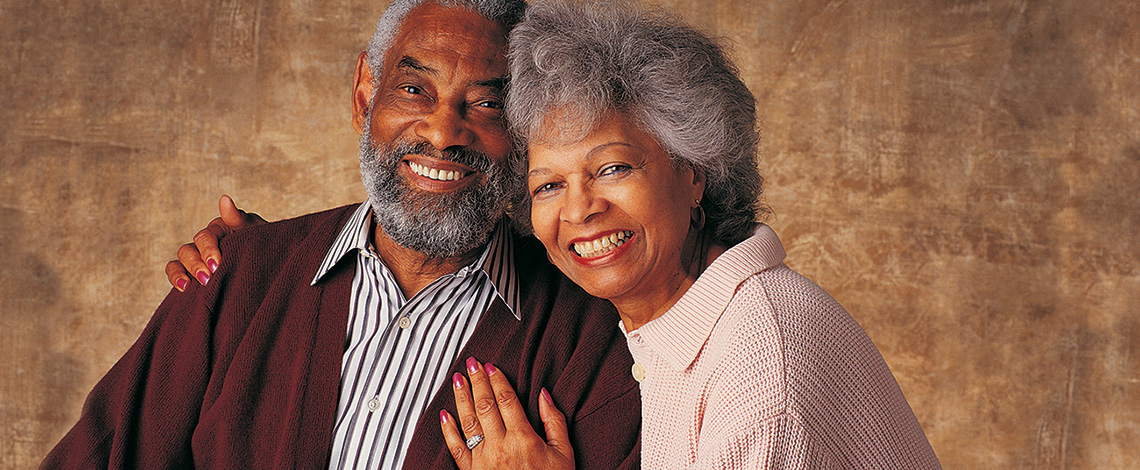 Elderly couple leaning in toward each other with a big smile on their faces