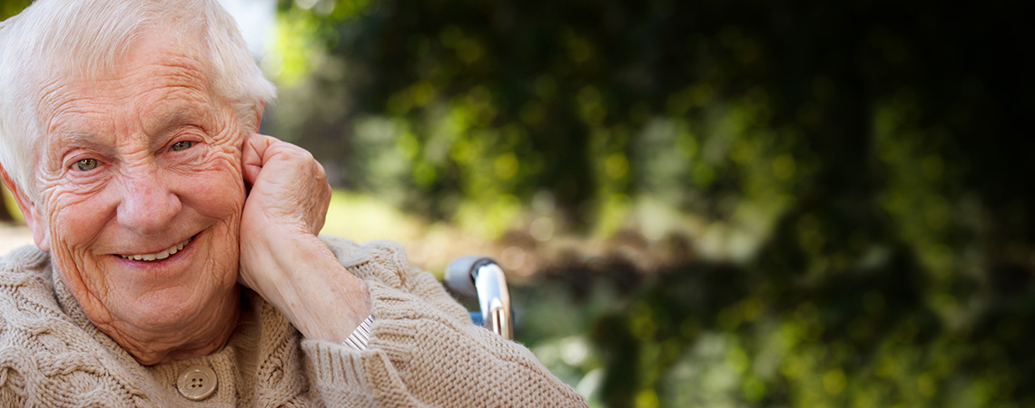 Elderly Man in a wheelchair outside smiling