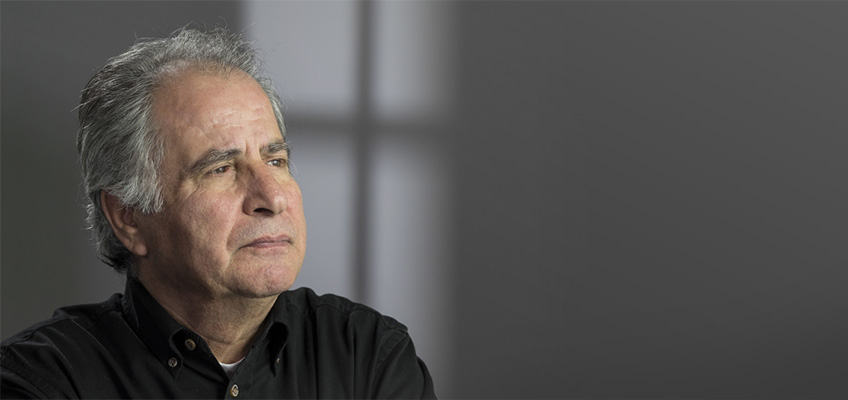 A man in a darkened room looking into the distance