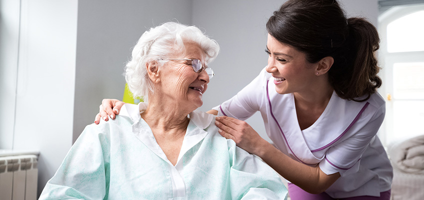 A nurse leaning in toward a resident smiling