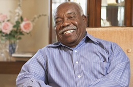An older male sitting in a chair smiling
