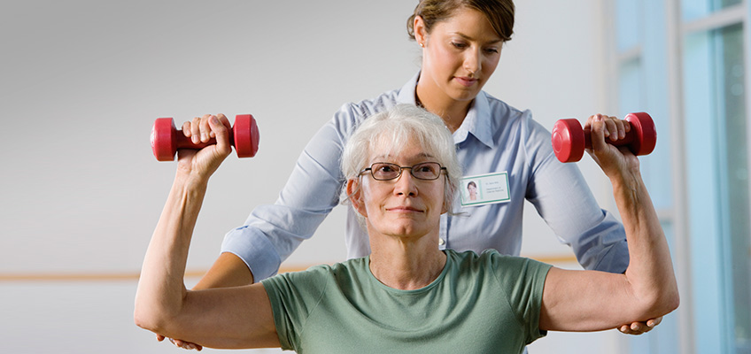 A staff member assisting a patient while she is lifting up dumbbells