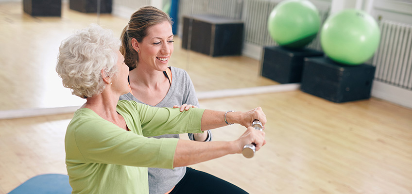 A woman assisting an older woman with dumbbell exercises in a gym setting