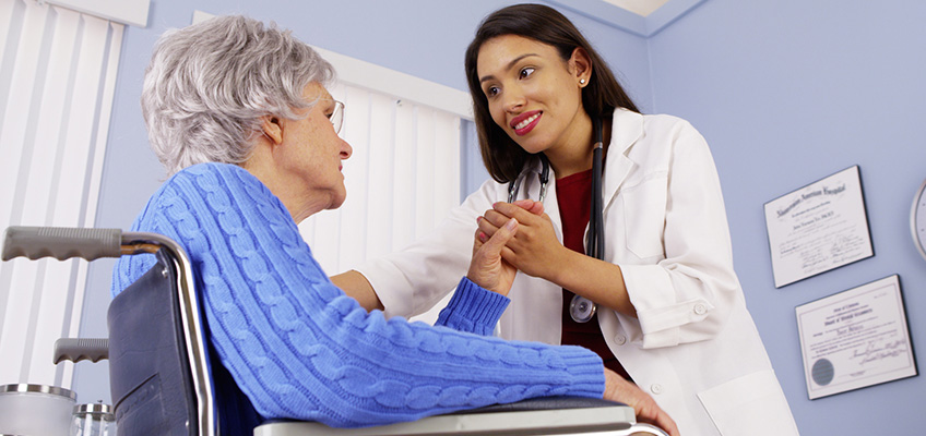 A nurse leaning in toward a patient in a wheelchair holding her hand