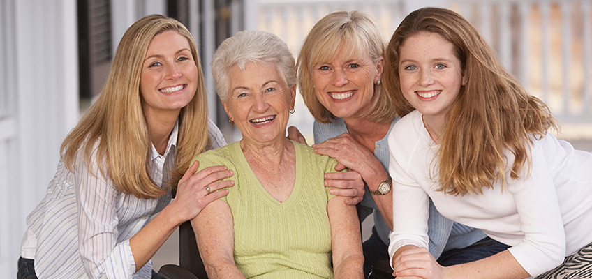 A family surrounding a grandmother outside smiling