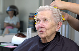 An older woman having her hair done in a salon