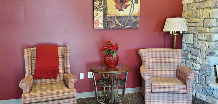 Corner niche decorated with red plaid upholstered chairs next to a stone fireplace