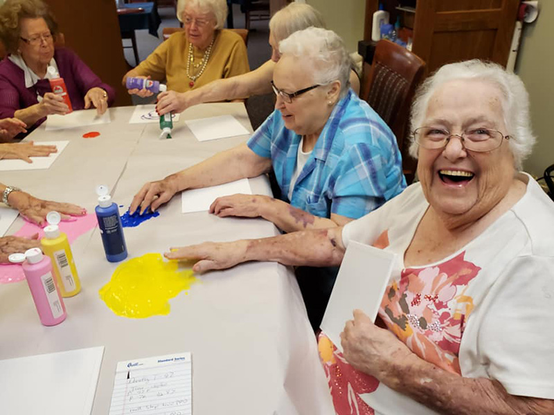 Senior ladies enjoying a crafting session of finger painting