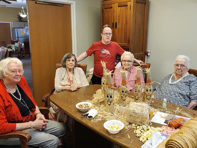 Residents displaying their fall crafts of clear glass bottles decorated and filled with hay