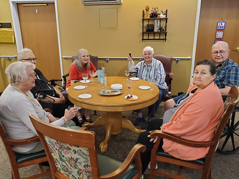 Six residents enjoying wine, cheese, and crackers