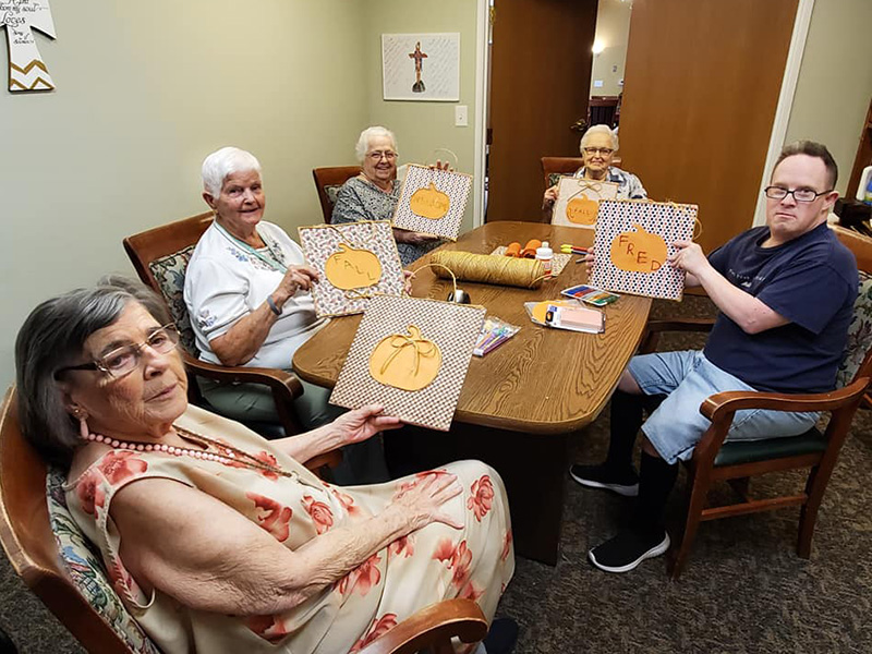 Five residents participating in a Fall craft activity
