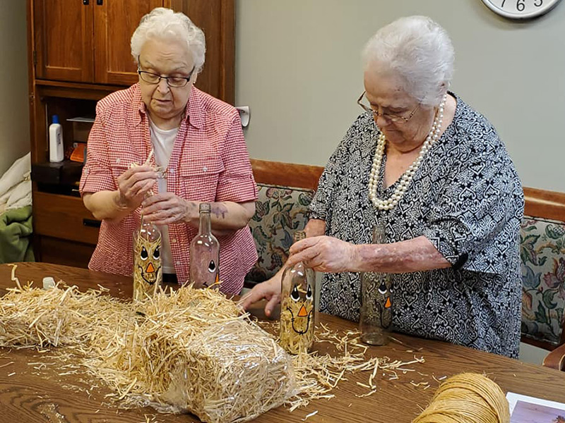 Two residents concentrating on a Halloween craft