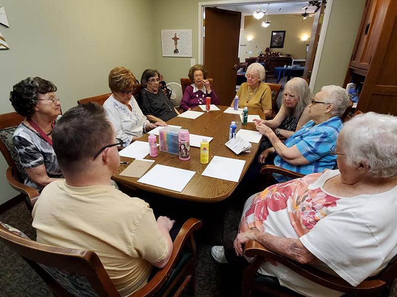 A meeting of a group of residents before the finger painting activity starts