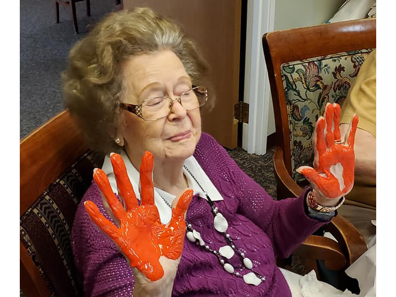 A resident with her hands covered in orange finger paints