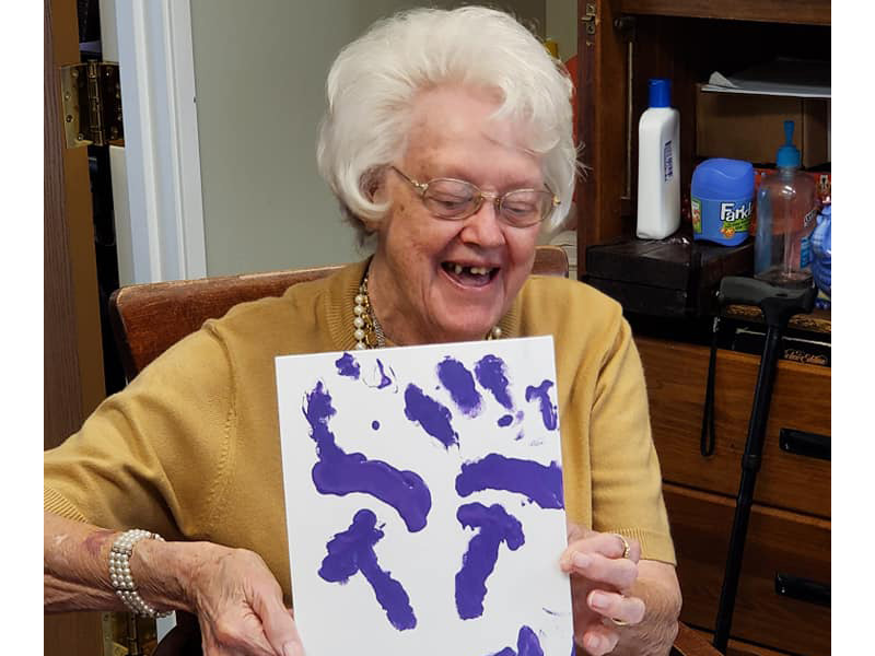 Smiling resident very proud of her purple finger painting activity