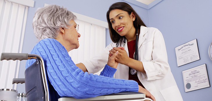 Nurse leaning down to speak with a patient in a wheelchair