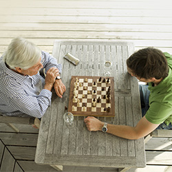 Two men playing a game of chess at a table.