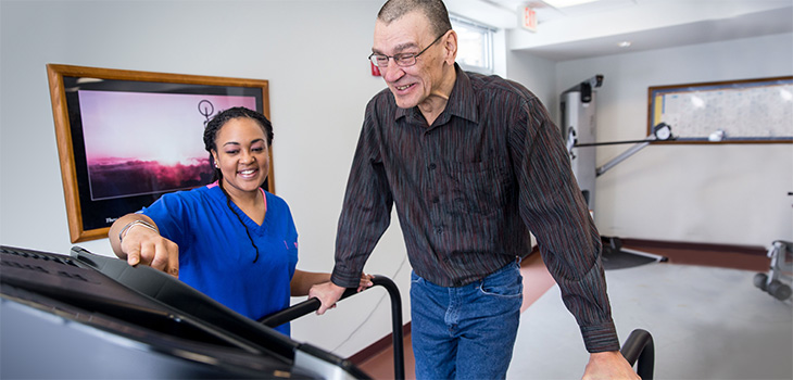 Resident smiling while using the treadmill and working with a therapist