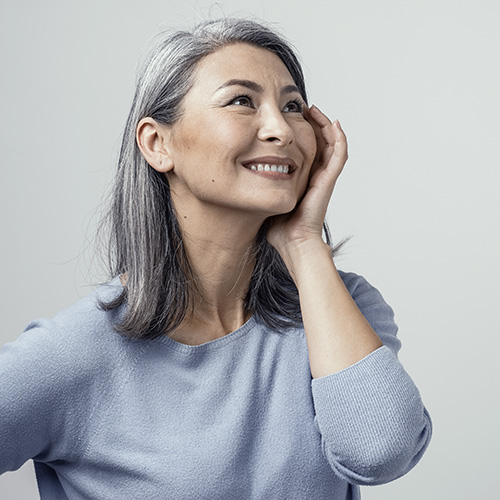 Woman with grey hair looking off into the distance